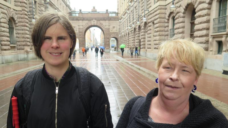 Ida Östlund och SRF:s Lena Ridemar i halvfigur i regn framför riksdagshuset.