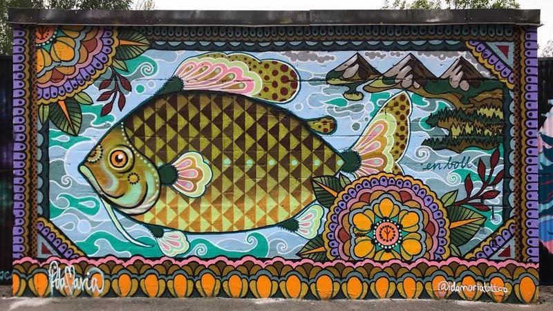 En stor muralmålning på en vägg. En stor tecknad tropisk fisk i gröna toner, blå vågor bakom.En bord kantar bilder, mandalamönster i orange och lila.