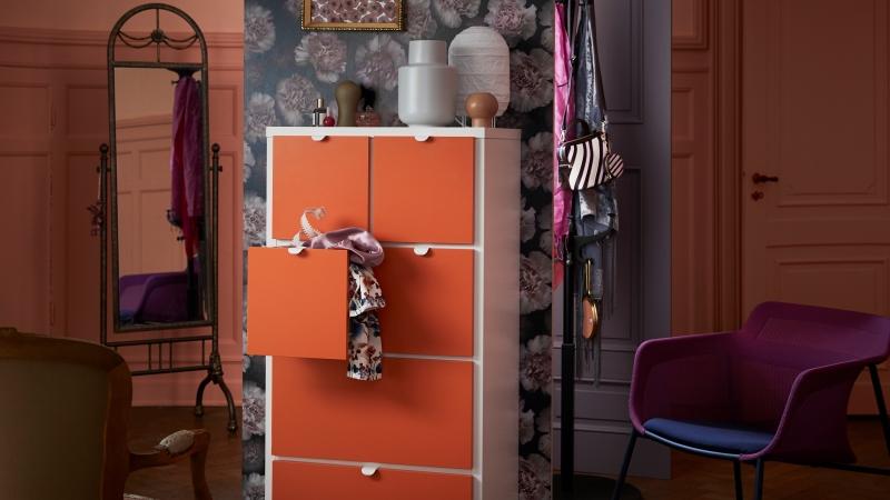 Foto ur Ikeas katalog. Del av färgglatt rum med fokus på en hög, vit byrå med stora orange lådor framför en storblommig tapet. Mönstrade kläder på en klädhängare och en lila fotölj intill.
