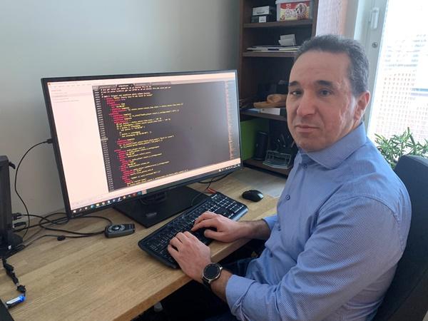 Medelålders man med lätt gråsprängt mörkt hår och mörka ögon sitter vid en stor dataskärm klädd i ljusblå skjorta.
