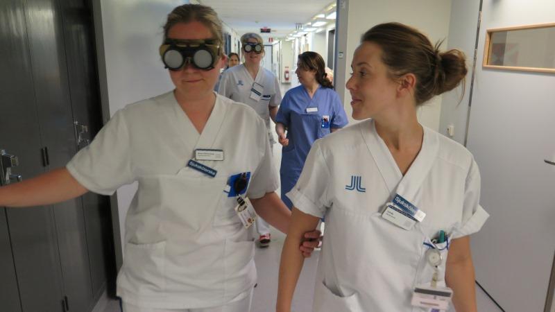 Skjuksköterskor provar stora glasögon som ger illusion av synnedsättning.
