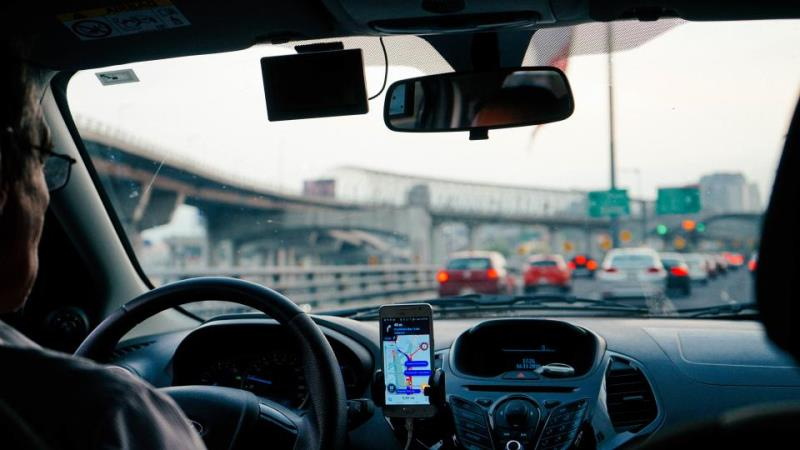 Bild tagen från baksätet i en bil, genom framrutan köer och vägskyltar i oskärpa.