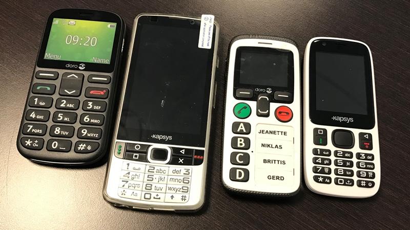Fyra mobiltelefoner i olika utföranden ligger intill varandra på ett bord.