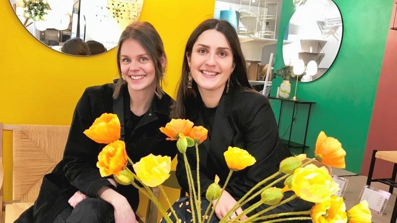 Två unga kvinnor sitter bredvid varandra, knallgul vägg bakom, stor bukett gula blommor i vas framför.