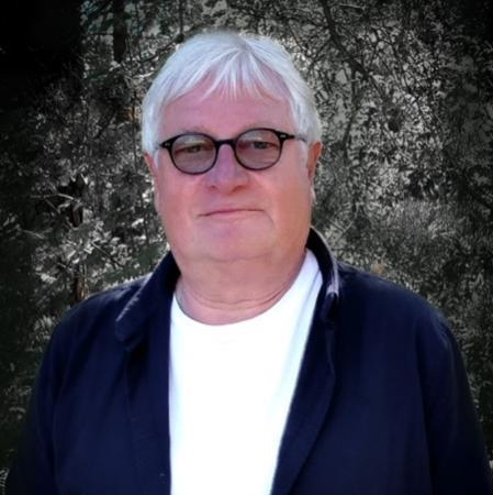Man med vitt hår och lugg i pannan, runda svarta glasögon med lätt tonade glas. Klädd i vit tröja under mörkblå jacka.