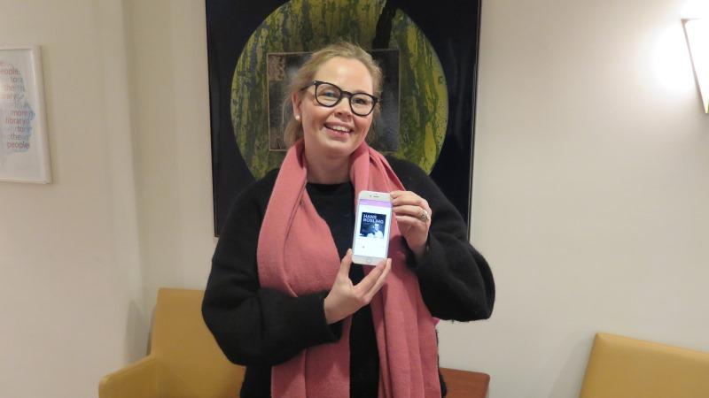 Leende blond kvinna med glasögon och håret i tofs håller upp en mobiltelefon.