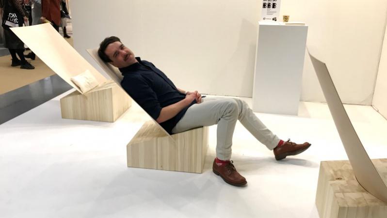 En man mörkt kort hår, halvligger i en träfåtölj på en möbelmässa