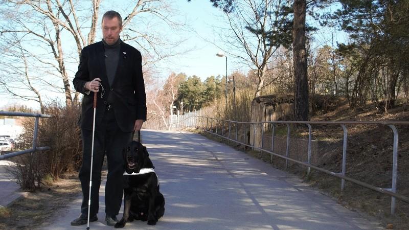 En man med mörkblont hår och kort skägg, klädd i mörk kavaj och grå polotröja står med vit käpp och ledarhund på en gångväg.