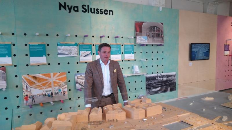 Man i grå kavaj står framför en modell av Slussenbygget.