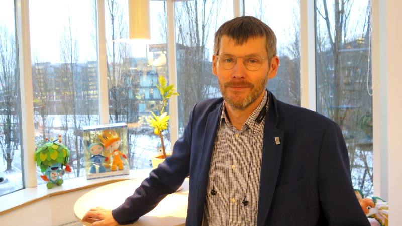 Johan Strid är klädd i skjorta och kavaj, har kortklippt mörkt hår, gråsprängt skägg och runda glasögon.