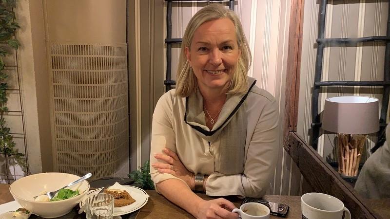 En blond kvinna med halvlångt hår sitter vid ett kafébord. Hon bär en ljus tröja med lång vid krage.
