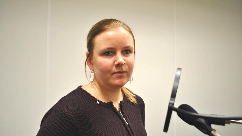 En blond ung kvinna i halvbild med uppsatt hår, sitter i en studio vid en mikrofon.