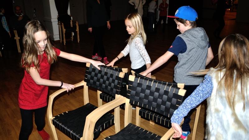 """Fyra barn tar sig runt uppställda stolar i leken """"Hela havet stormar"""""""