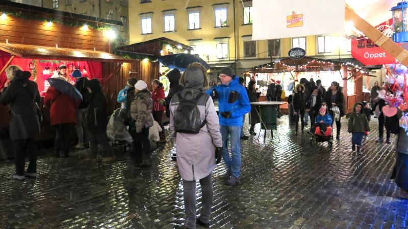 Stortorget i Gamla stan. Besökare i förgrunden, röda julbodar och julbelysning längs fasaderna.