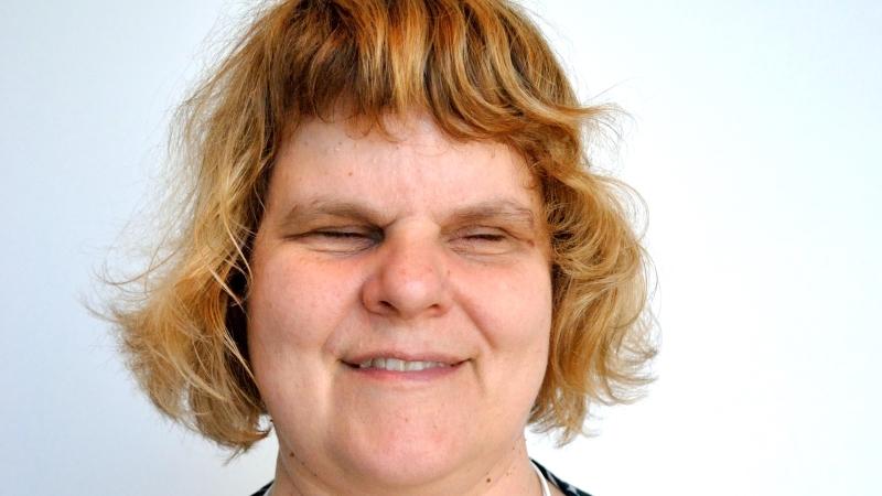 Närbild på kvinnoansikte, kort blont hår, lite lockigt. Det är Karin Hjalmarsson