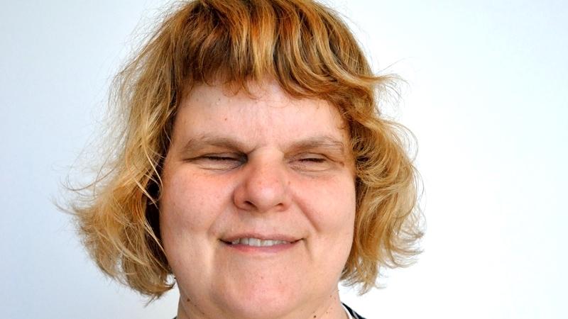 Leende kvinna i närbild med rödblond page med lugg.