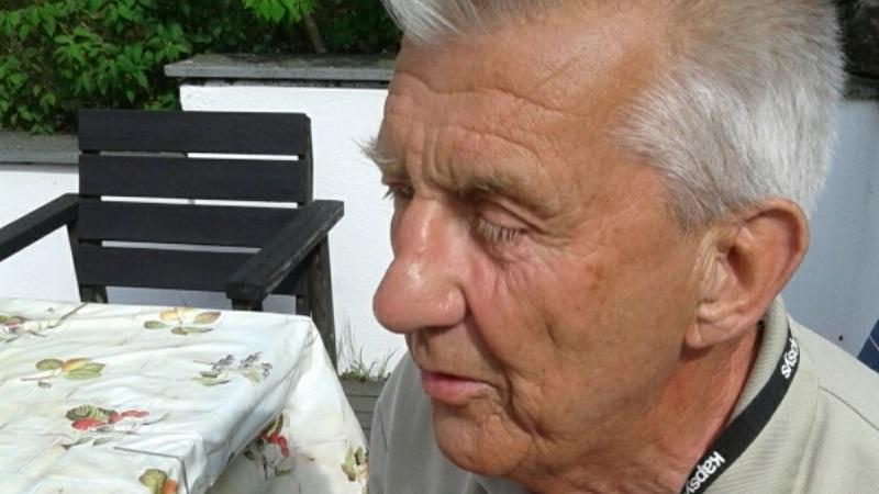 Närbild på en äldre man med halvslutna ögon, vitt hår och ansiktet till hälften bortvänt.