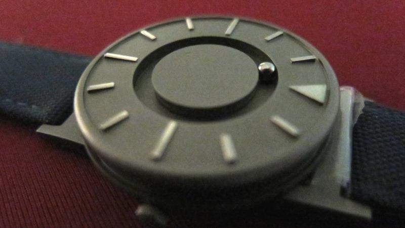 Bild på taktil klocka där det istället för visare finns kula som rullar i en cirkelformad skåra.