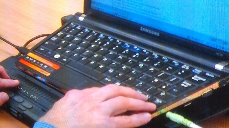 Händer på punktskriftstangenter framför en laptopskärm.