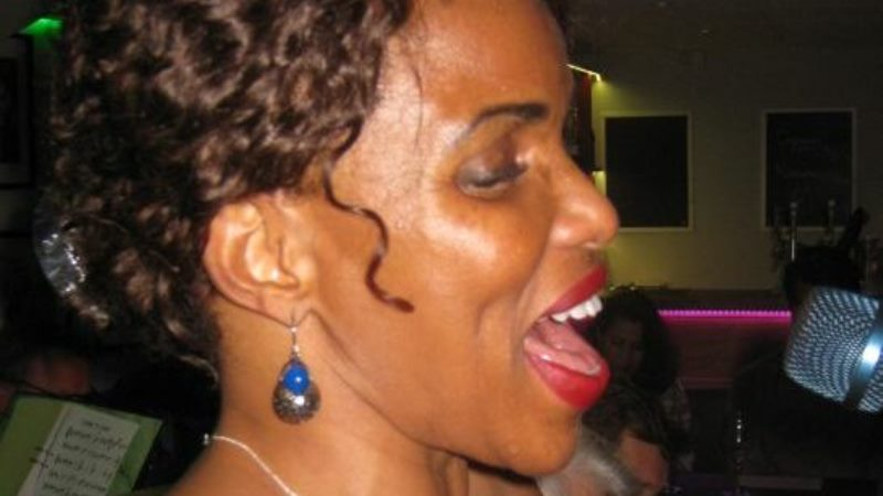 Kvinna med mörk hy och uppsatt lockigt hår sedd i profil framför mikrofon.