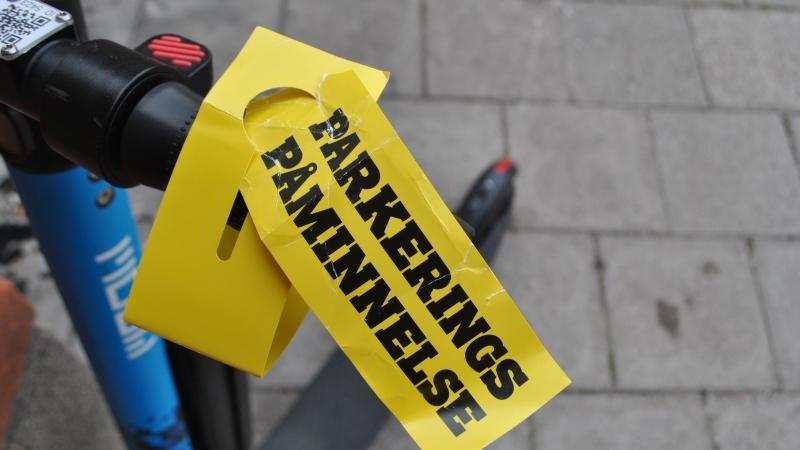Närbild på en stor klargul lapp med varningstext i svarta versaler: PARKERINGSPÅMINNELSE. En elsparkcykel skymtar i bakgrunden.
