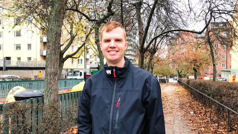 En ung man står i en park. Han har kort ljust hår, en blå tunnare jacka. Halvbild.
