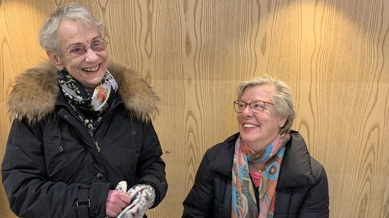 En leende äldre kvinna med grått hår och glasögon i mörk jacka med pälskrage står till vänster. Till höger sitter en något yngre kvinna med blont hår och glasögon i en mörk jacka och färgglad halsduk. Hon ler och tittar på kvinnan till vänster.