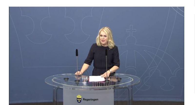 Lena Hallengren har halvlångt blond hår och står vid ett talarbord med mikrofoner.