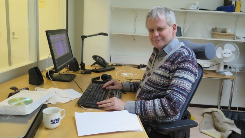 Lennart Karlsson, ombudsman för SRF. Han har kort, ljusgrått hår och randig tröja och sitter vid sitt skrivbord framför datorn. På bordet finns också en hög med punktskrift och en kaffekopp.