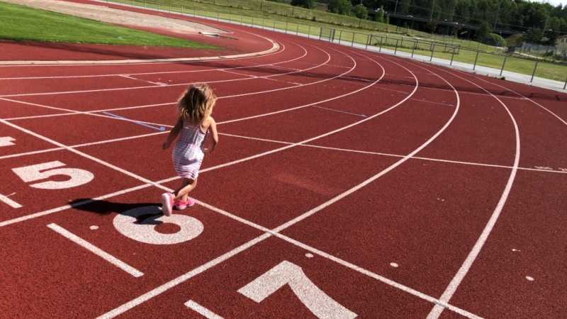 En liten blond flicka i ljus sommarklänning springer på en roströd löparbana.