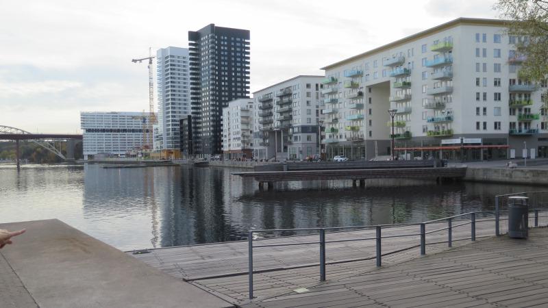 Vy från en kaj med bostadshus, Årstabron längst bort, två höghus sticker upp mellan lägre hus och lyftkranar skymtar emellan.