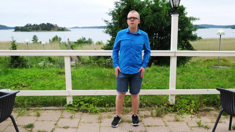 Ung man med snaggat blont hår, små glasögon med svarta bågar samt blå skjorta och blå shorts.