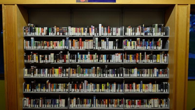 En stor biblioteksbokhylla fylld med ljudböcker med ryggarna utåt.