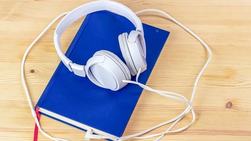 Ett par vita hörlurar ligger ovanpå en bok med blått omslag. Kontaktpluggen är instucken mellan bokens blad.