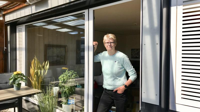 Blond kortklippt kvinna med glasögon lutar sig mot en dörren till en altan.