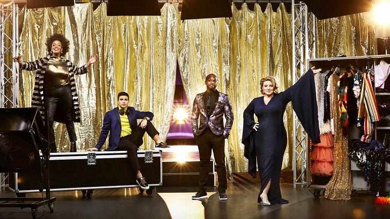 Programledarna Marika Carlsson, Eric Saade, Kodjo Akolor och Sarah Dawn Finer utspridda framför en guldridå i galakläder. Foto: Magnus Ragnvid/SVT.