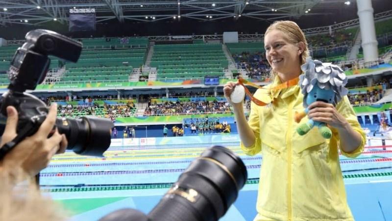 Maja Reichard efter sitt silver på 50 meter frisim i Paralympics 2016. Hon ler brett, har långt, blont hår och är klädd i en gul sportjacka. Foto Karl Nilsson