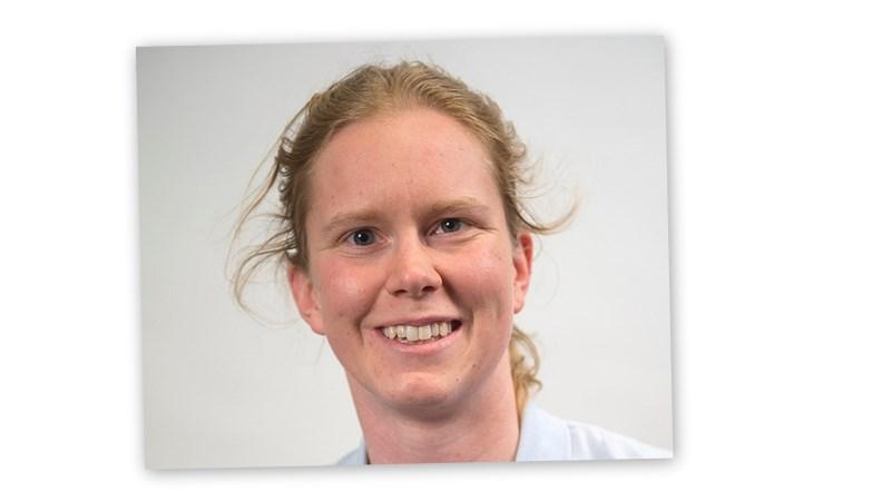 Simmaren Maja Reichard har det blonda håret i tofs i nacken och ler brett