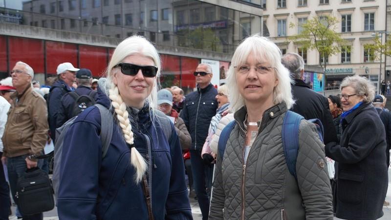 Två kvinnor framför en folkmassa. Anne-Lie Telning till vänster har det ljusa långa håret samlat i en fläta och mörka glasögon och Ditte Kahlström Jansson har kort blont hår, glasögon och grön jacka.