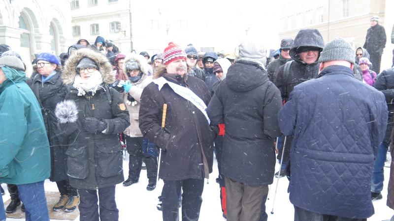 SRF:s ordförande Håkan Thomsson i färgglad mössa omgiven av påpälsade mötesdeltagare i snöstorm.