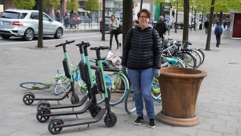En kvinna i jeans och en mörk jacka står i stadsmiljö mitt i bild, på vänster sida står flera elsparkcyklar parkerade, till höger finns en stor terrakottakruka.