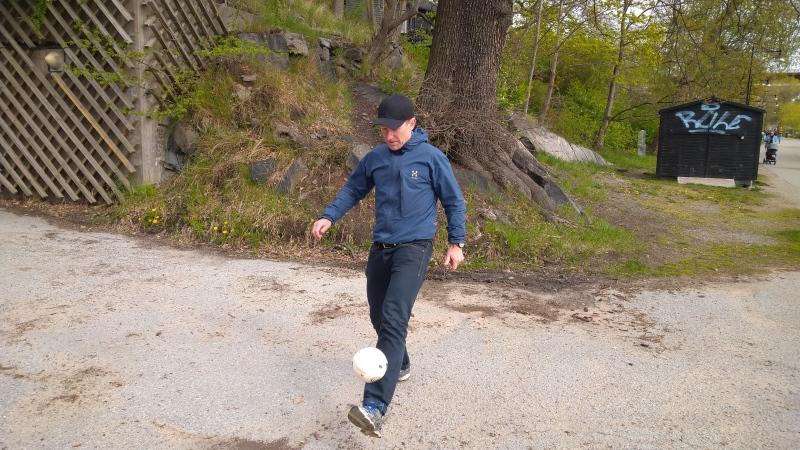 Man i blå träningsjacka med byxor sparkar en fotboll
