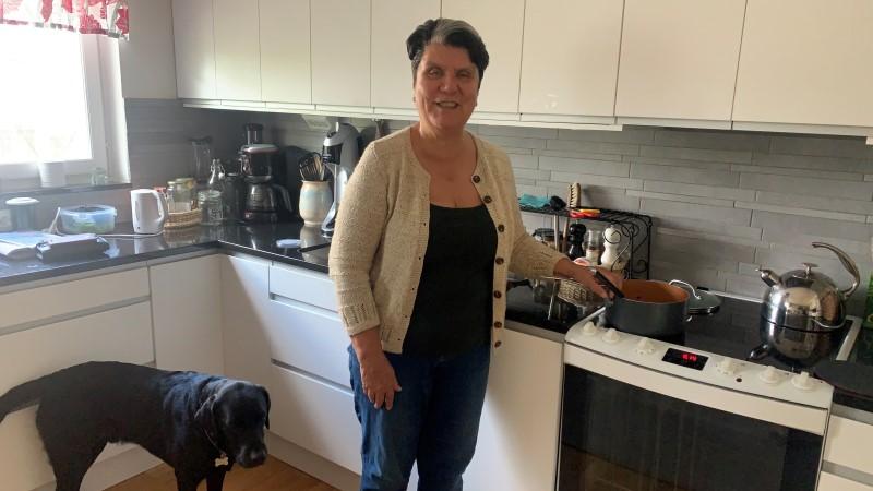 Kvinna står i sitt kök, vid spisen. I bakgrunden köksbänken med köksredskap. Bredvid henne står hennes ledarhund, en svart labrador. Kvinnan har mörkt kort hår, en beige stickad kofta, svart tröja under, mörkblåa byxor.