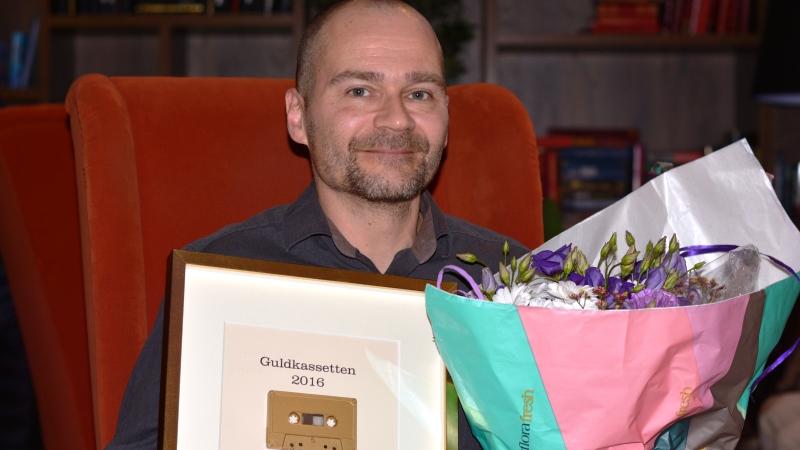 Bild på Mats Sundling med diplom och blommar.