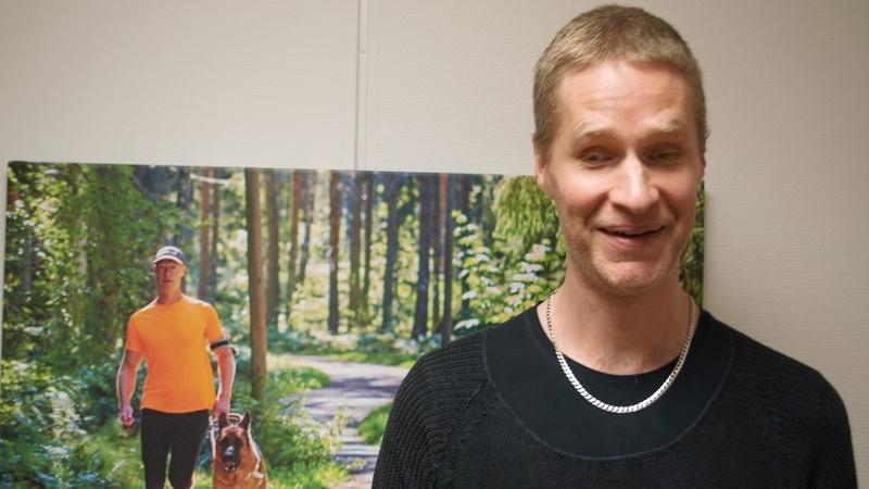 En leende man med kort, blont hår och ljus skäggstubb står vid en affisch i skogsmiljö med en sportklädd man som joggar med ledarhund.