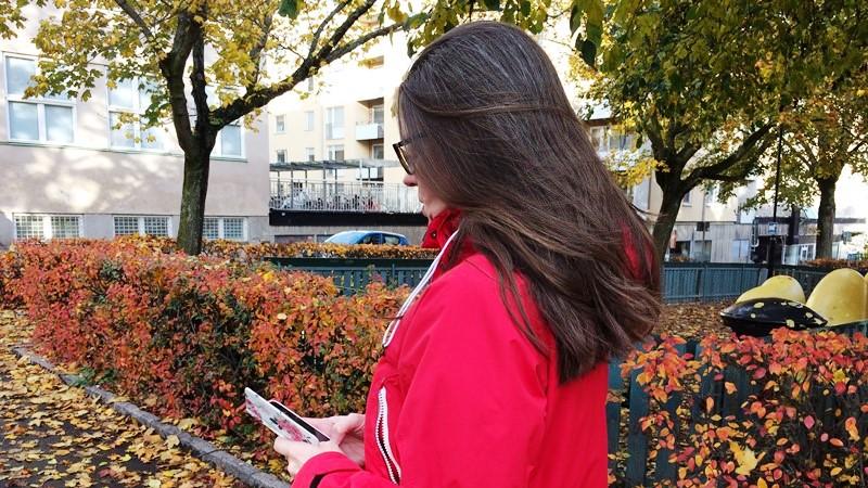 Bild bakifrån: Kvinna med mörkt hår och röd jacka, går och tittar ner på mobilen. Träd i bakgrunden.