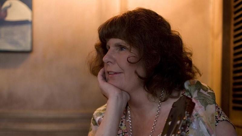 Monica Söderberg sitter till höger i bild och tittar till vänster, med huvudet stött på höger hand. Hon har lockigt mörkbrunt hår, och bär ett halsband av länkar och en blommig klänning. Halsen av en gitarr skymtar i förgrunden.