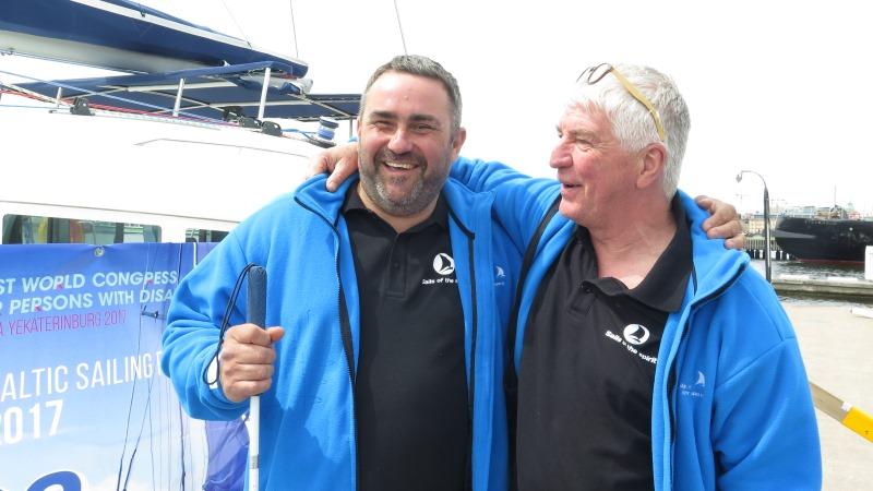 Två glada medelåldersmän i likadana blå jackor står med armarna om varandras axlar.