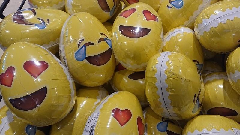 Mängder av gula påskägg med emoji-mönster. Leende ansikten med ögon som antingen är hjärtformade, eller ihopknipta springor med tårar av skratt i ögonvrån.