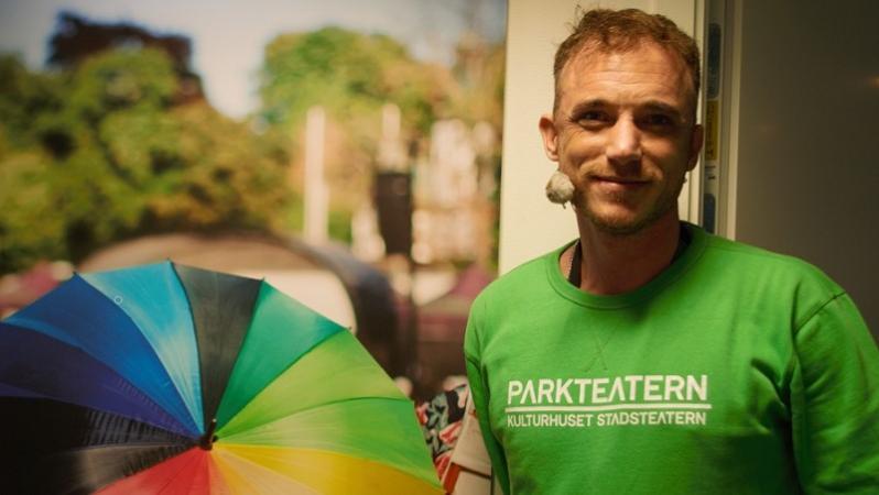Till höger i bild står Albin Flinkas i en ljusgrön tröja med texten Parkteatern. Han är kortklippt med rufsigt hår och skäggstubb. Till vänster i bild finns en plansch med ett regnbågsfärgat paraply.
